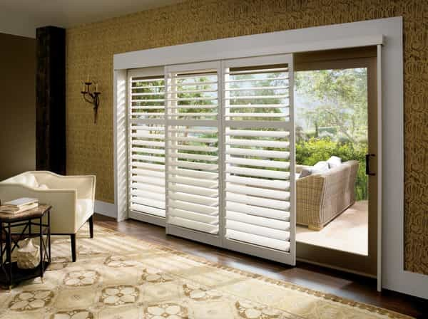 Shutter Sliding Patio Door — Wide Louvers that tilt open and tilt close. Shutter window treatment using a By-Pass Track System. Panels stack behind one another