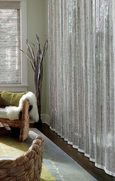 Natural Shade Drapery Woven — A vertical drapery for the patio door opening in ivory and misty grey offer elegance and beauty.